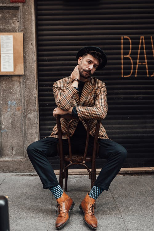 Charismatic stylish man on chair in city
