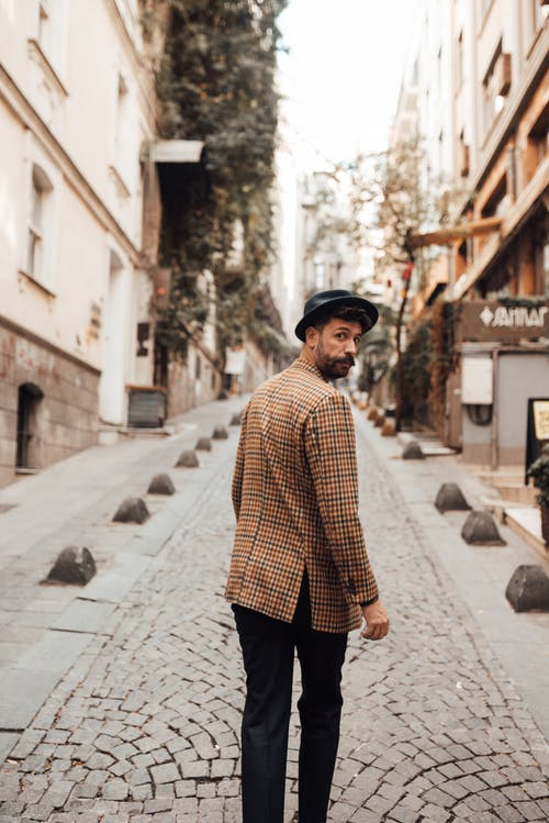 Back view of stylish male hipster with beard and hat strolling on cobblestone street while looking over shoulder