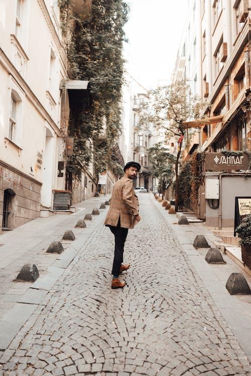 Man walking along narrow paved street
