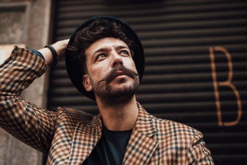 From below of thoughtful bearded male in trendy outfit touching hat while looking away