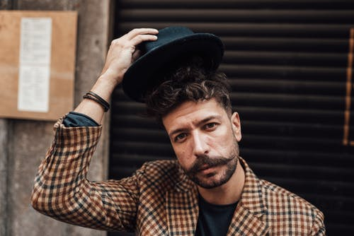 Handsome male model with trendy haircut and beard taking off hat while standing near building and looking at camera