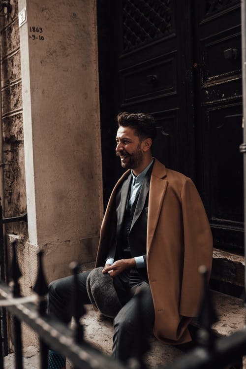 Charismatic bearded male in formal clothes sitting on stone stairs near wooden door and looking away with smile