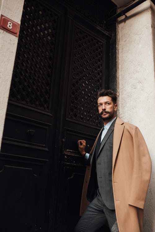 From below of handsome male hipster in elegant suit and coat opening door of old building while looking away