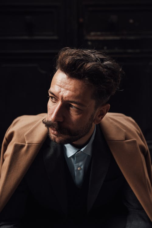 Confident adult male with trendy hairstyle and mustache in formal clothes looking away pensively