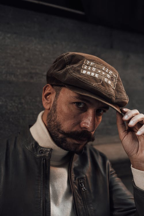 Confident bearded male model with mustache in black leather jacket touching hat while looking at camera