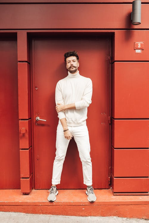 Full body of male model in monochrome white outfit standing in doorway and looking at camera