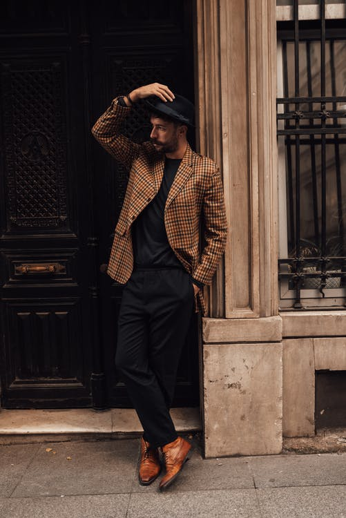 Full body of confident male in trendy outfit holding hand in pocket and touching hat while looking away