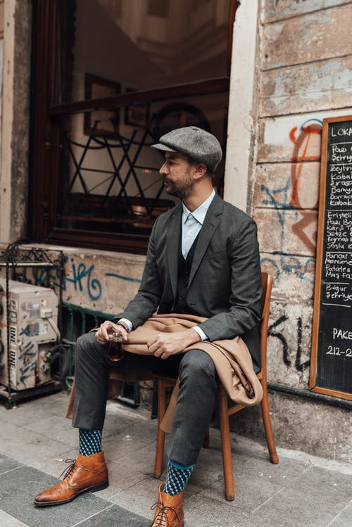 Serious male hipster in trendy outfit holding glass of tea while sitting on chair on street