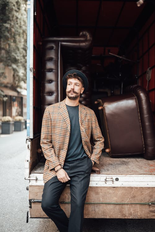 Confident male hipster holding hand in pocket while standing near trunk with leather furniture and looking away