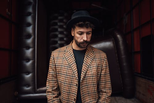 Pensive man in trendy outfit against sofas