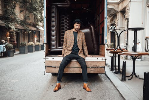 Full body of stylish male in trendy suit spreading legs while sitting on trunk and looking at camera