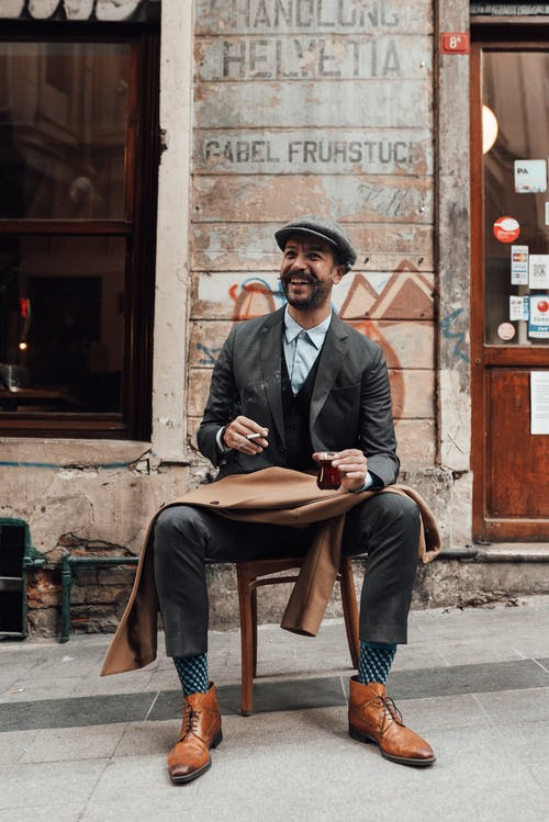 Delightful bearded male sitting on pavement with hot drink and smoking cigarette