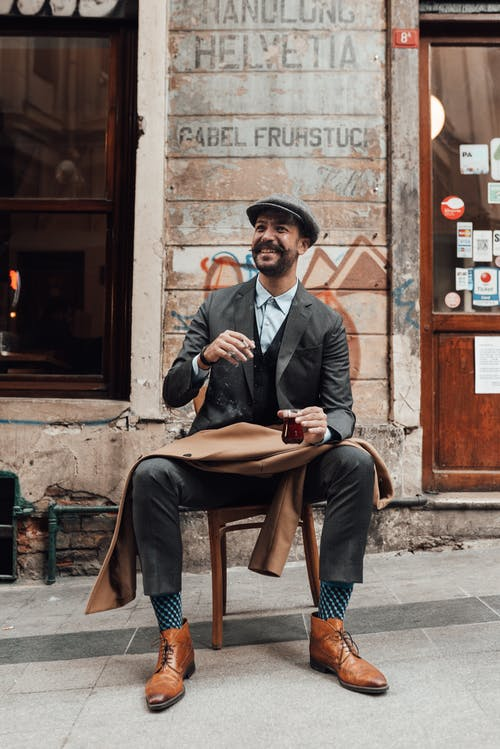 Cheerful stylish bearded guy resting with cigarette and glass of drink