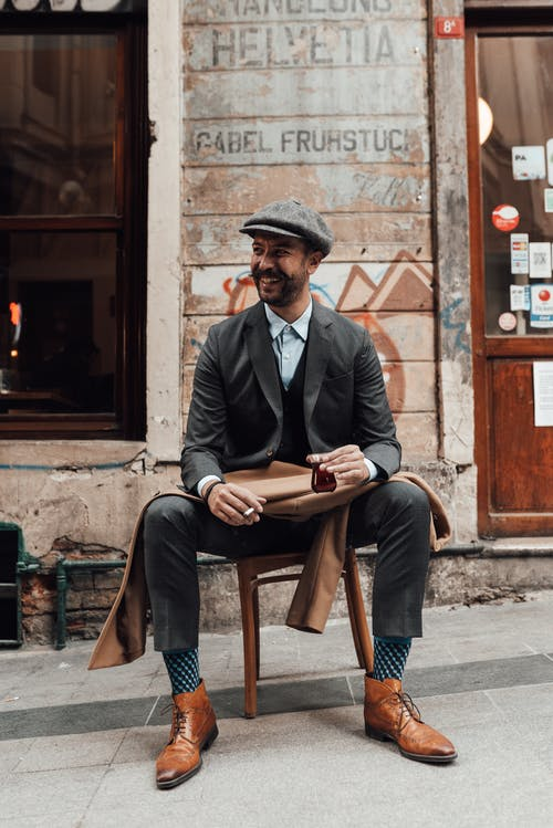 Full body of satisfied guy wearing stylish outfit resting in street near shabby building with hot beverage and cigarette in daylight