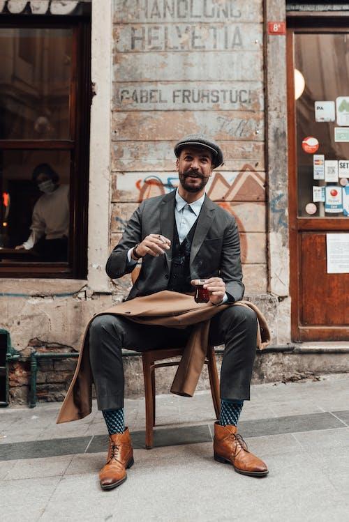 Smiling adult man in suit having coffee break near cafeteria