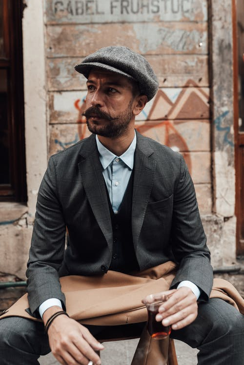 Man with mustache wearing classy outfit drinking tea on street
