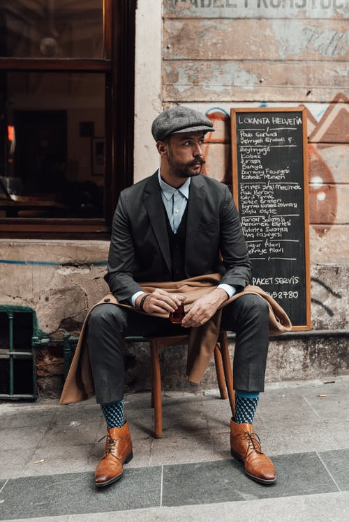 Thoughtful bearded male with mustache and glass of tea in classy outfit looking away while resting on stool on street