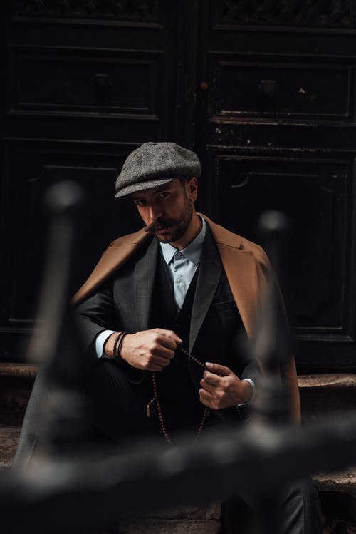 Serious male with beard and mustache in formal suit and stylish coat sitting on stairs of building and looking at camera in daytime
