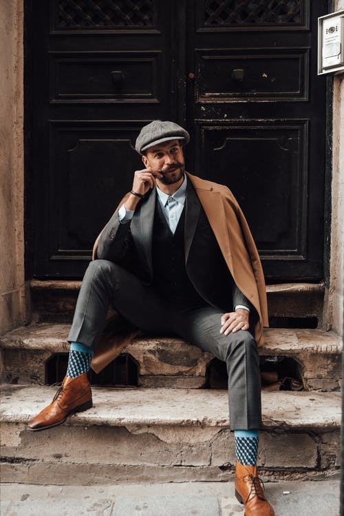 Pensive man with mustache and beard in stylish formal clothes sitting on stairs against door of building and looking away in daytime