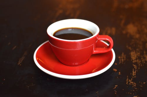 Cup of hot coffee on ceramic saucer