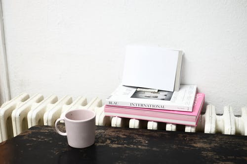 Ceramic cup on table near radiator with books