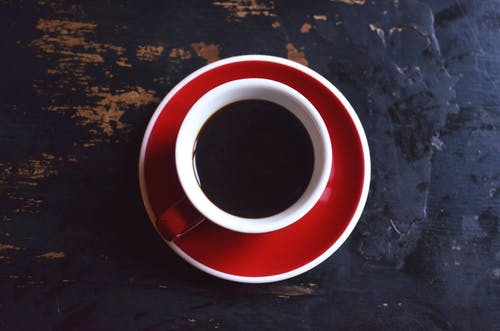 Top view of red ceramic cup of hot aromatic black coffee with saucer placed on shabby wooden table