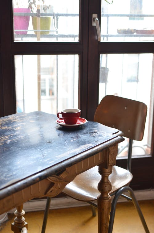 From above of shabby wooden table with red ceramic cup of hot tasty beverage near balcony door in morning