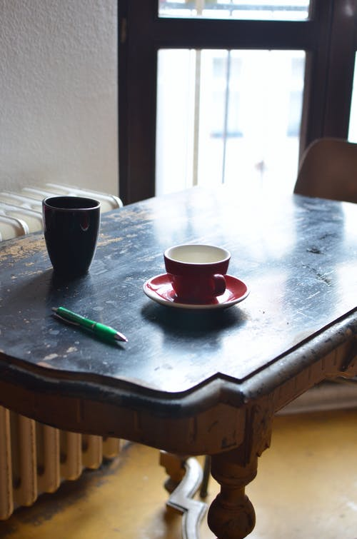 Cups of hot drinks on wooden table near radiator