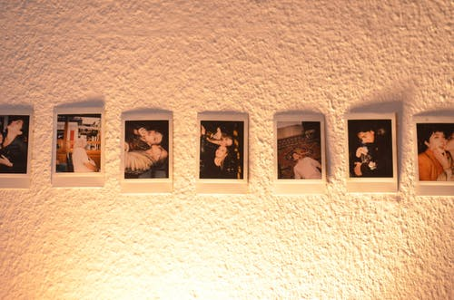 Set of colorful instant printed pictures placed on texture white wall in dark room illuminated with nightlight
