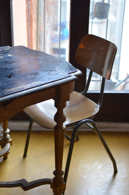 From above of aged shabby wooden table and chair placed near balcony door in room