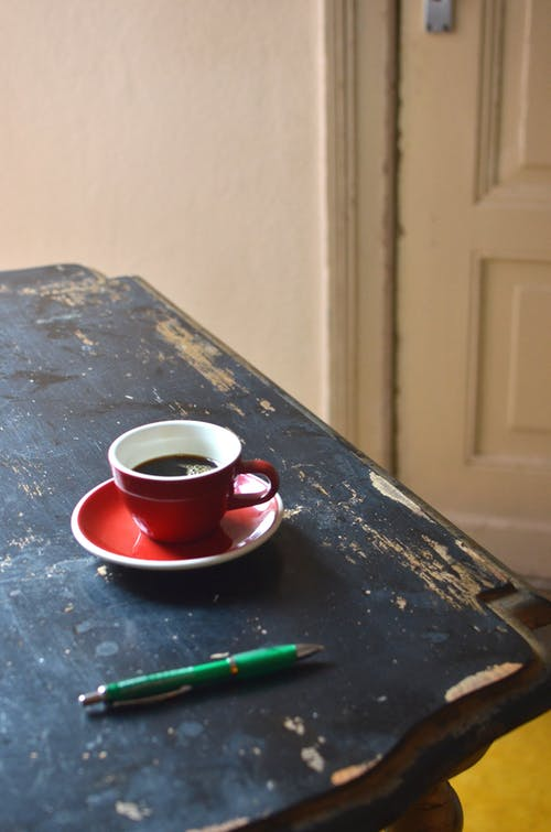 Pen and coffee in cup on wooden table