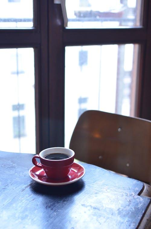Cup of coffee on table near balcony door