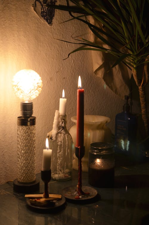 Vintage glowing lamp placed on table near burning candles in candlesticks in dark room