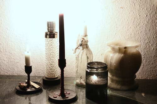 Glowing lamp illuminating dark room placed on table near burning candles on candlesticks and empty ceramic vase