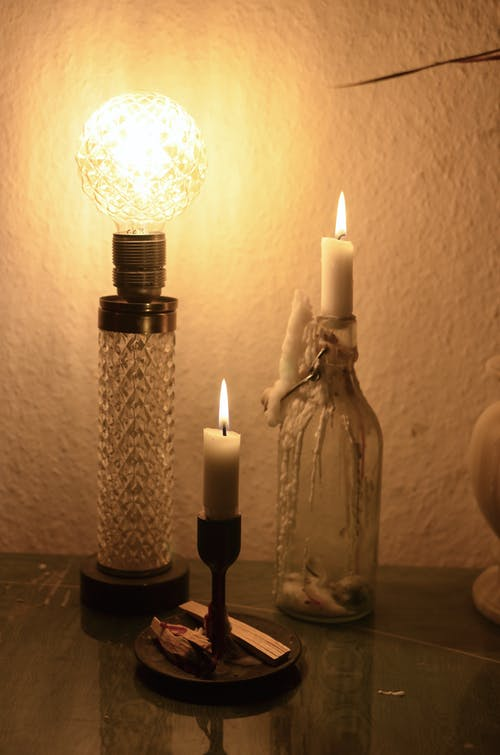 Lamp on table near candles and bottle