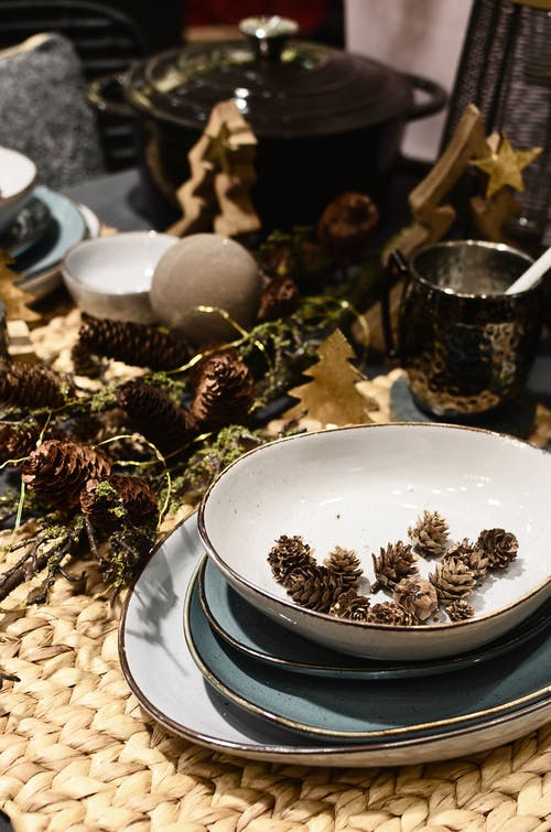 Porcelain plates and bowl with fir cones near New Year decor on straw mat in house