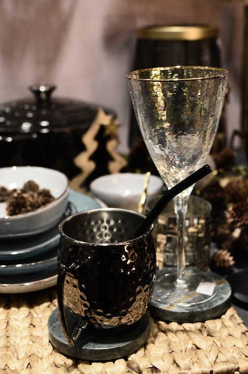 Metal pitcher near glass and dishware with pine cones on wicker mat during Christmas holiday in house