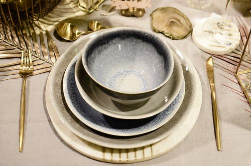 High angle of table setting with ceramic bowls and plates between cutlery on decorative sprigs