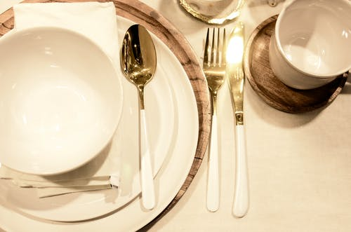 From above of porcelain dishware with napkin and wooden stand on served table during celebration