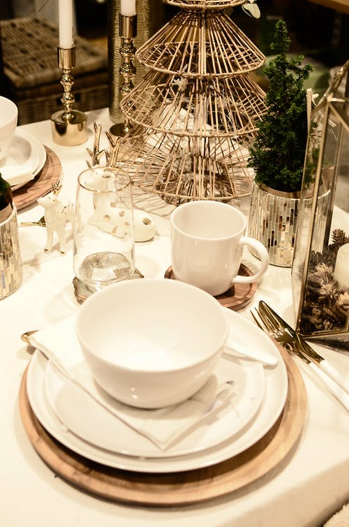 From above of served table with set of dishware near decorative deer statuettes and small Christmas tree during festive event in restaurant