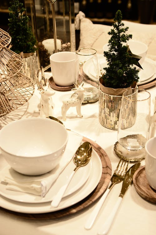 From above of served table with small Christmas tree and decorative deer statuettes during festive event in restaurant
