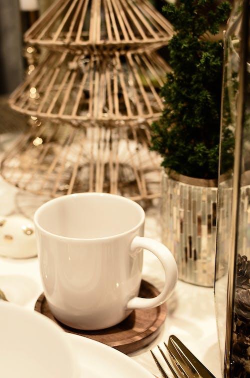Ceramic mug near small Christmas tree on table