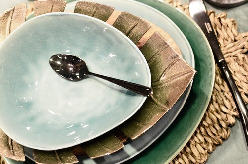 From above of served table with ceramic bowl and plates with spoon and knife on straw mat in restaurant
