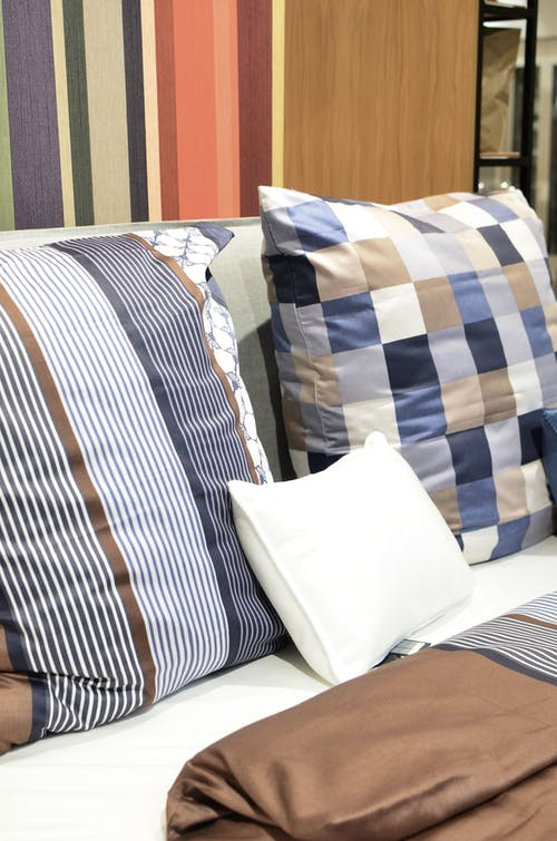 Creative design of assorted cushions with ornament on soft bed against color palette in bedding shop