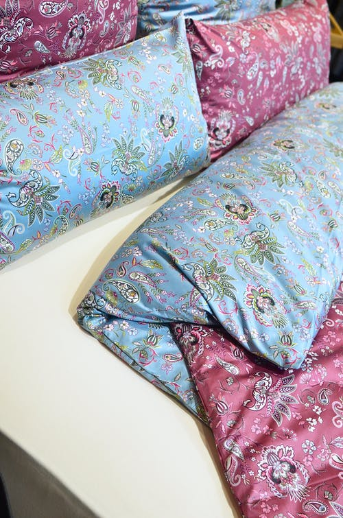 From above of assorted decorative pink and blue pillows near blanket on soft bed