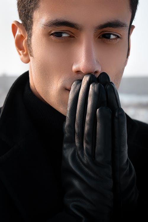 Crop thoughtful young male with clasped hands in black leather gloves near face looking away