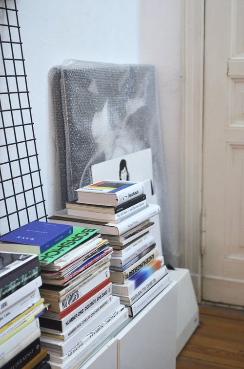 Heaps of textbooks with hardcovers and inscriptions near white door at home with wooden floor