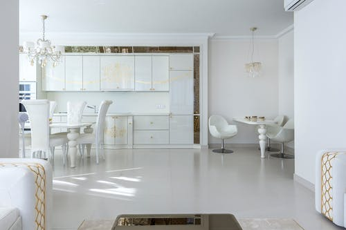 Interior of contemporary apartment with light dining zone and white furniture in kitchen
