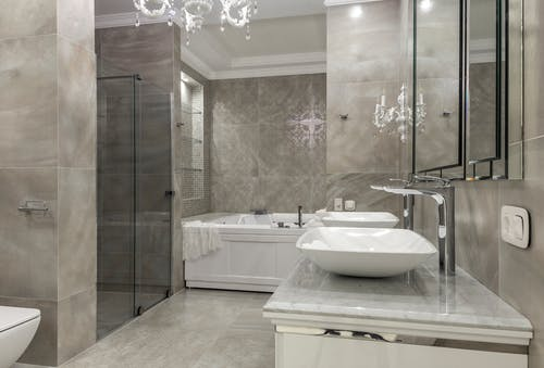 Luxury interior of spacious bathroom with tiled walls and floor double vessel sink vanity and chandelier