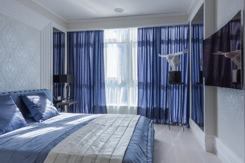 Pearl and blue interior of modern bedroom with comfortable bed and elegant decorations